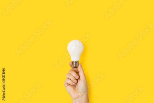 Obraz Mano sosteniendo una bombilla blanca sobre un fondo amarillo liso y aislado. Vista de frente y de cerca. Copy space - fototapety do salonu