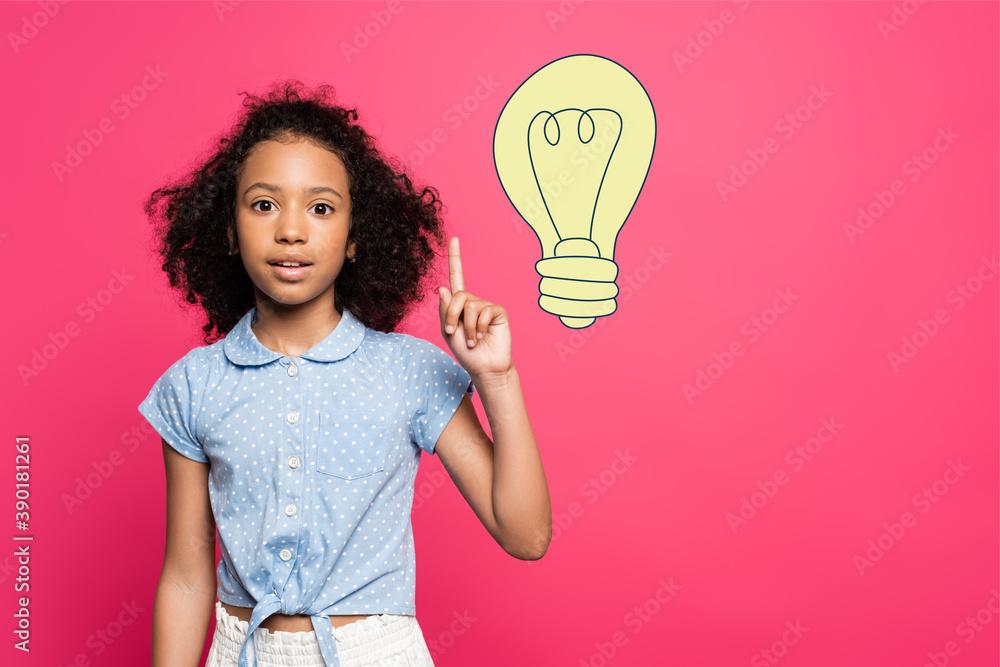 Fototapeta curly african american child showing idea gesture near light bulb illustration on pink