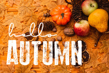 Top View Of Autumnal Decoration And Food Scattered From Wicker Basket Near Hello Autumn Lettering On Golden Foliage