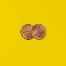 Front And Back Of Two Pennies On Yellow Background