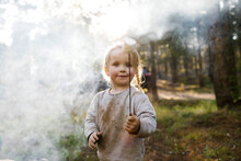 Portrait Of Girl (2-3) Holding Marshmallow Near Campfire In Forest, Wasatch Cache National Forest