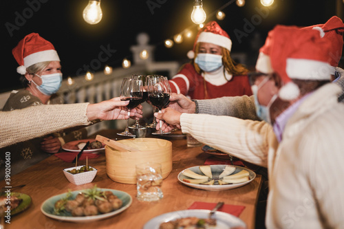 Happy senior people celebrate christmas together and cheering with red wine whil Canvas