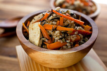 Close Up Of Brown Rice Bowl With Carrot And Hijiki Served On Table