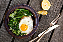 Close Up Of Pan Seared Asparagus Salad With Frisee And Fried Egg Served On Plate