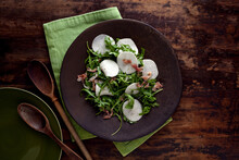 Overhead View Of Turnip Salad With Arugula And Prosciutto Served On Plate