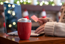 Woman In Sweater Holding Credit Card Using Laptop For Making Order Sitting At Table Near Christmas Fireplace With Decoration Of Light Bulbs. Online Booking, Reservation. Travel Concept