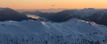 A Single Engine Airplane Flying Through Snowy Mountains At Sunset