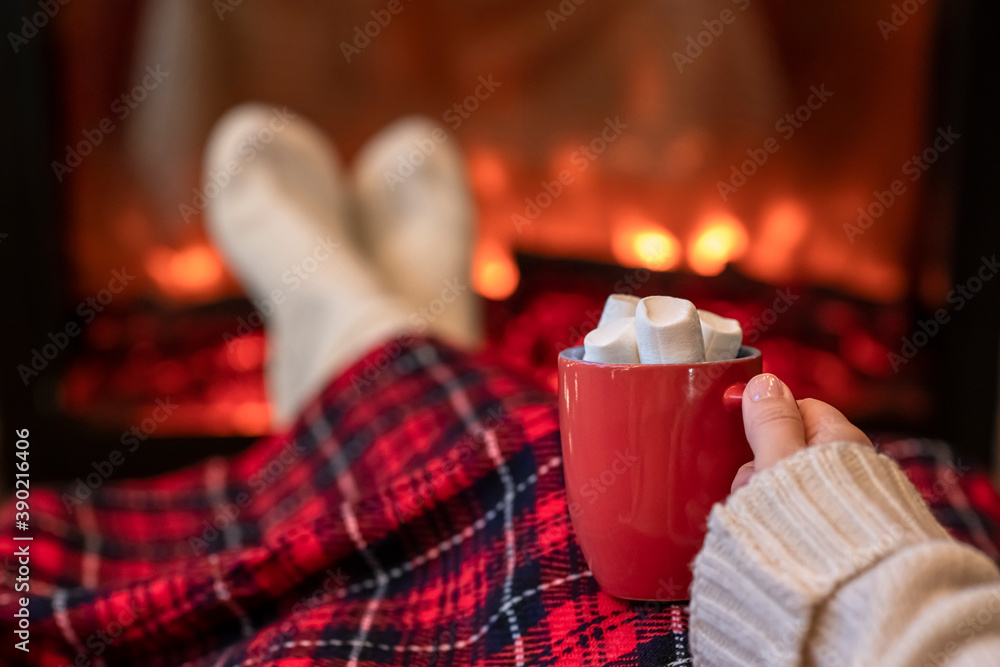 Fototapeta Woman with cup of hot cocoa and marshmallow warming legs in winter white socks near fireplace flame, covered christmas plaid