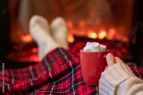 Carta da parati Woman with cup of hot cocoa and marshmallow warming legs in winter white socks n