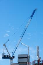 Large Construction Cranes On Site Against A Brilliant Blue Sky