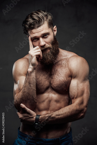 Obraz Bearded and shirtless guy with modern haircut and huge biceps posing with finger to his head in dark background. - fototapety do salonu