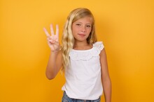 Beautiful Caucasian Young Girl Standing Against Yellow Background Showing And Pointing Up With Fingers Number Three While Smiling Confident And Happy.