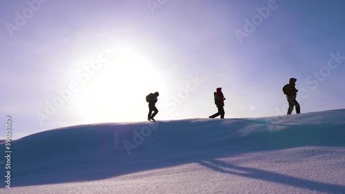 Tela Travelers walk along top of a snowy ridge in the rays of the beautiful sun
