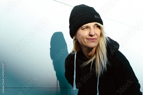 Obraz na plátně Portrait of a rude woman with a maleficent smile, looking away, wearing a wool cap, in a white background of the street