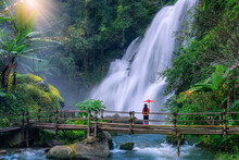 Asian Woman Tourist  Stands On A Bamboo Bridge Watching Pha Dok Siew Waterfall At Doi Inthanon National Park, Chiang Mai Province, Thailand