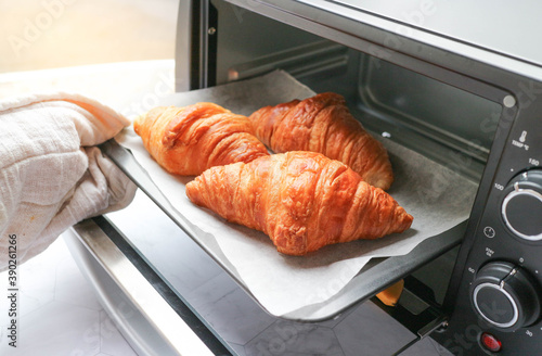 Fototapeta Croissant was taken out from mini oven ready to serve - Morning breakfast concept obraz