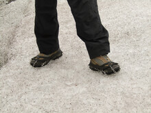 Women's Feet With Hiking Shoes And Crampon For Traction, Walking On Alaska Glacier.