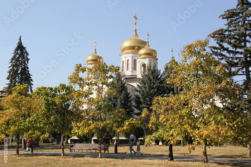 Fotografiet View of white Orthodox Church with golden domes in the park.