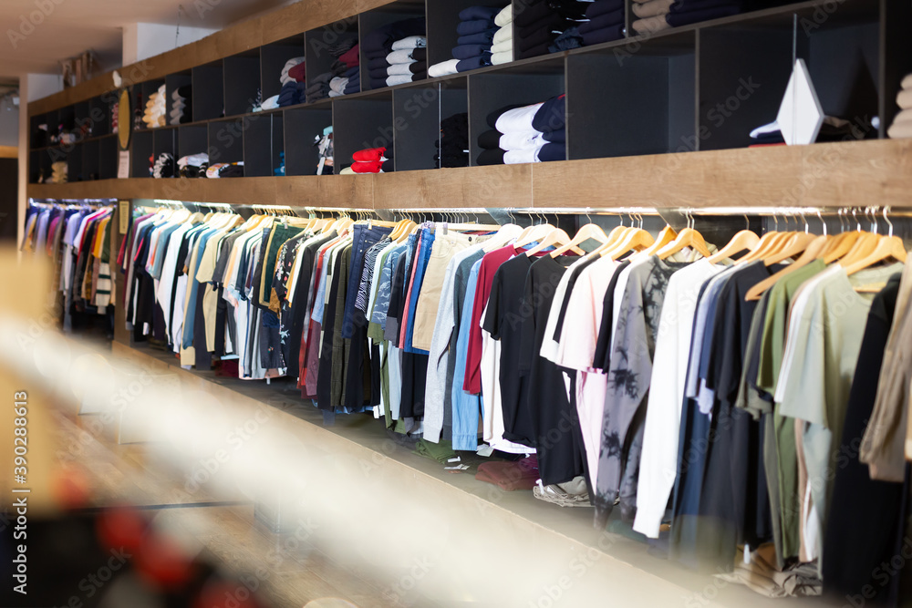 Fototapeta Men clothing shop, assorted casual clothes on hangers and shelves in apparel store