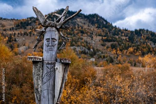 Fotografija Wooden totem pillar on mountains background in autumn