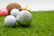 Golf Ball With Christmas Ornament On Green Grass
