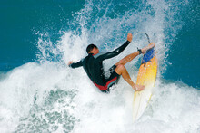 A Surfer Carves A Radical Off-the-lip And Sends Spray Flying From A Wave In The Ocean.