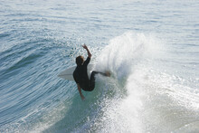 A Surfer Carves A Radical Cutback On An Ocean Wave In The Early Morning Light.