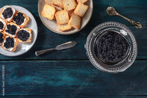 Fotografie, Obraz Caviar in a vintage bowl and on toasts, with a spoon and knife, overhead flat la
