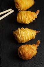 Closeup Shot Of Potato String Shrimps On A Black Board