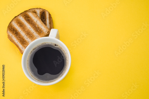 Obraz na plátne High angle shot of a cup of coffee and toasts on a yellow surface
