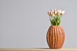 Modern embossed ceramic vase with tulips on a gray background with a copy space