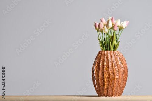 Fotografie, Obraz Modern embossed ceramic vase with tulips on a gray background with a copy space