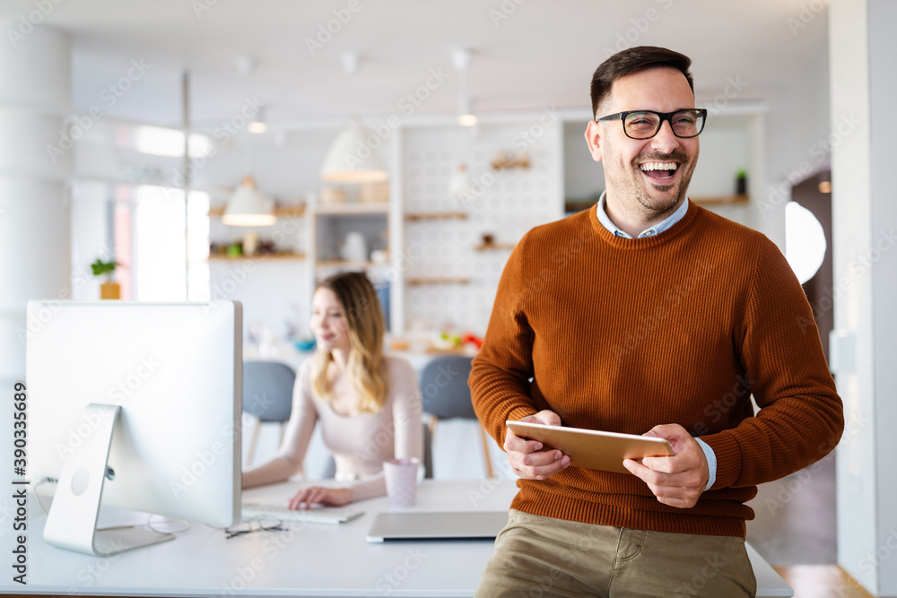Fototapeta Handsome businessman using tablet in office. Technology, business, people concept.