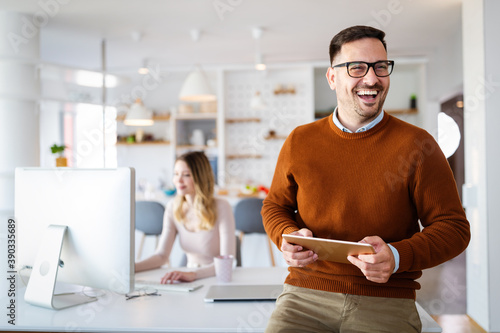 Obraz Handsome businessman using tablet in office. Technology, business, people concept. - fototapety do salonu