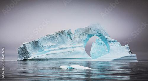 Papel de parede Iceberg bleuté creusé par l'érosion dérivant dans la brume au large des côtes du