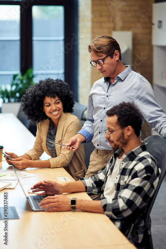 Three multiracial colleagues working together in the modern office, looking at laptop screen and discussing something
