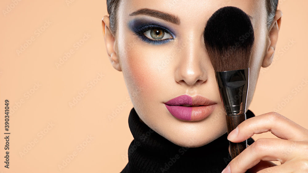 Fototapeta Portrait of a girl with cosmetic brush at face. Woman covering one eye on the face using makeup brush. One half face of a beautiful white woman with  bright makeup and the other is natural.