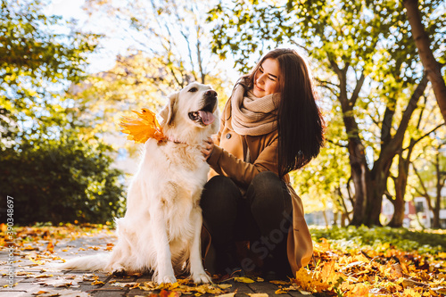 Fotografiet Young woman walk and play with her golden retriever in yellow autumn park
