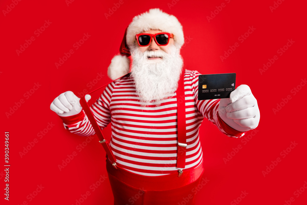 Fototapeta Portrait of his he nice handsome cheerful confident bearded fat Santa give you offer bank card payment service spend money budget having fun isolated bright vivid shine vibrant red color background