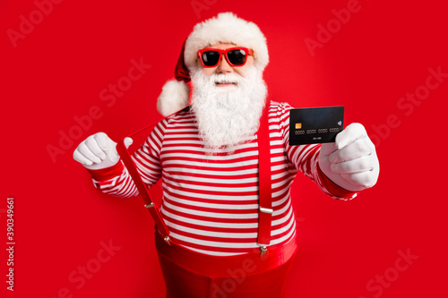 Fototapeta Portrait of his he nice handsome cheerful confident bearded fat Santa give you offer bank card payment service spend money budget having fun isolated bright vivid shine vibrant red color background obraz