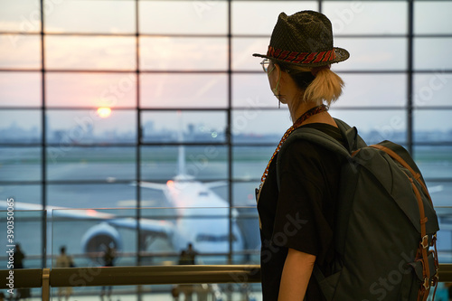 Fotografering asian woman female air traveler looking at sunrise in airport terminal building