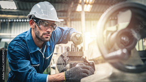 Male engineer in blue jumpsuit and white hard hat operating lathe machine Fotobehang