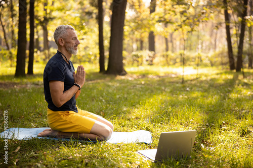 Fototapeta Calm mature male doing meditation with laptop outdoors obraz