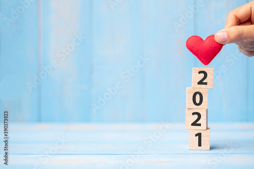 Fototapeta Business man hand holding red heart shape over 2021 wooden cubes on blue table background with copy space for text. Business, Resolution, New Year New You and Happy Valentine's day holiday concept obraz