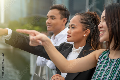 Photo Three asian young friends standing outdoor looking at the city skyline