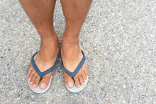 An Asian Man's Feet Are Wearing Old White Flip-flops, Blue Belt Straps. Standing On A Concrete Road, The Concept Of Poverty During The Crisis.