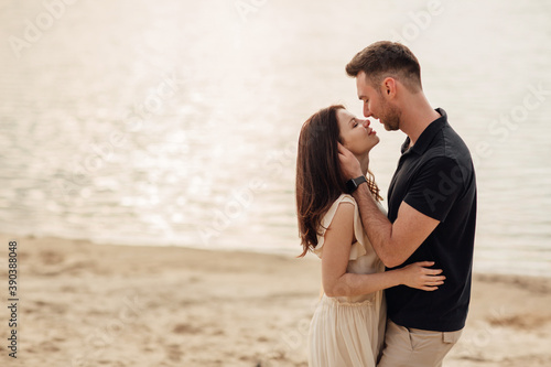 Romantic couple is hugging outdoors. elegant and stylish woman and man in love are walking along the lake. Happy moments together. love story