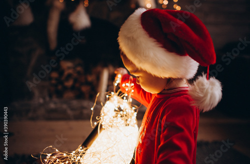 Canvastavla Little girl in red Santa costume is opening new tear presents and playing with lights near the Christmas tree by the fire place