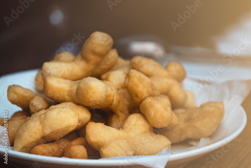 Fotografía Patongko or deep-fried dough sticks, traditional morning snack or breakfast of Thai and Chinese, close up Patongko or deep-fried dough sticks in white plate