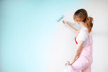 A Woman In A Pink Jumpsuit Is Painting A Wall. Renovation And New Life For Old Things.